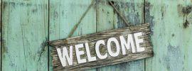 Welcome sign hanging on mint green wood door