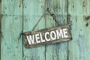 Welcome sign hanging on mint green wood door